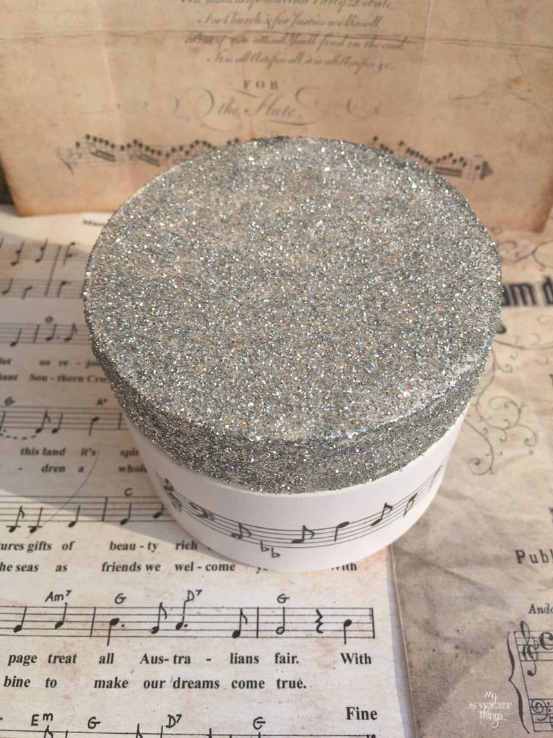 How to make a DIY Christmas Gift out of an old container using some glitter and music paper | Via www.sweethings.net
