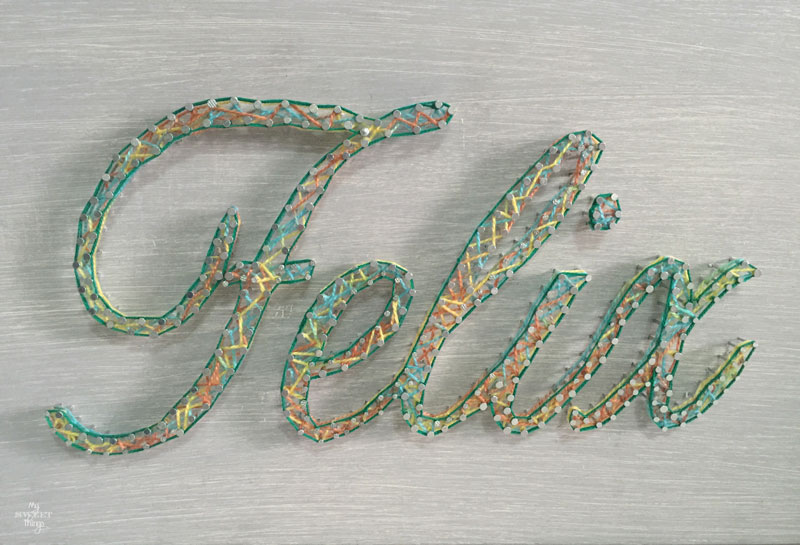 How to make an cool string wall art as a DIY birthday gift using a piece of scrap wood, some yarn and head nails